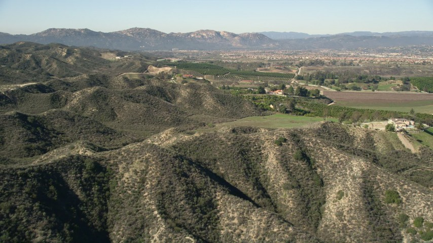5K stock footage aerial video fly over hills toward farmland, Temecula, California Aerial Stock Footage | AX0014_033