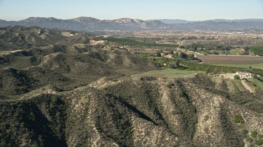 5K aerial video fly over hills toward farmland, Temecula, California Aerial Stock Footage | AX0014_033