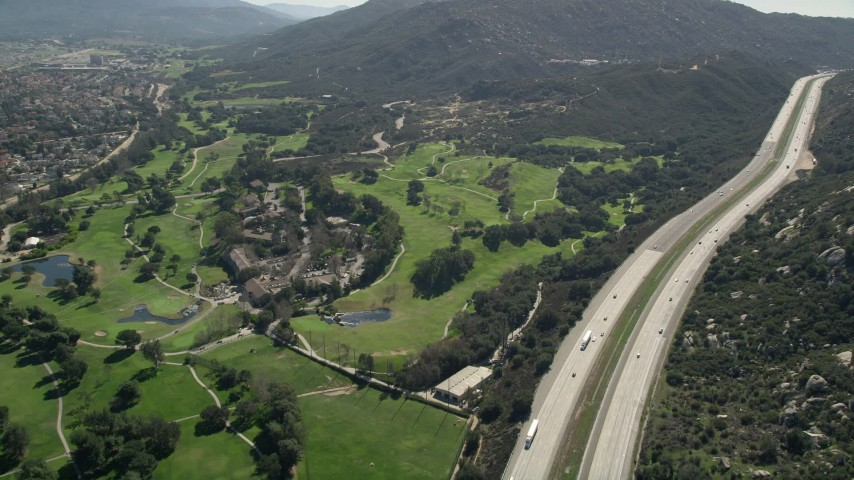 5K stock footage aerial video follow Interstate by golf course and hills, Temecula, California Aerial Stock Footage | AX0015_001