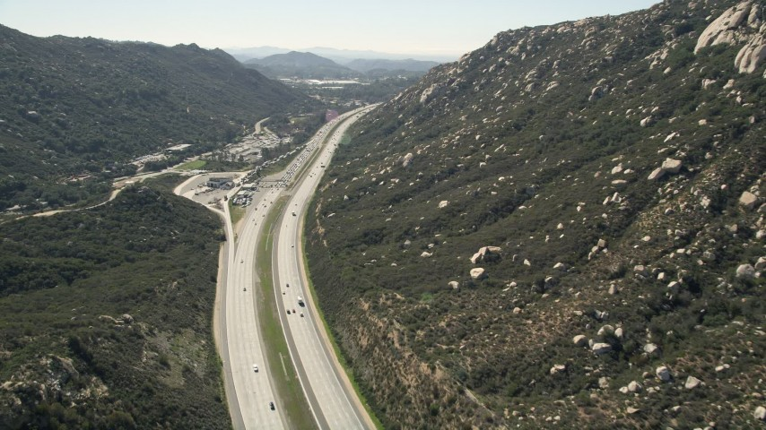 5K stock footage aerial video of interstate at the foot of mountains, Temecula, California Aerial Stock Footage | AX0015_003