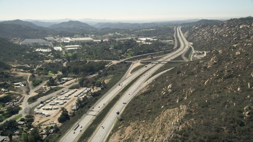 5K stock footage aerial video follow light traffic on an interstate through hills near greenhouses, Temecula, California Aerial Stock Footage   AX0015_006E