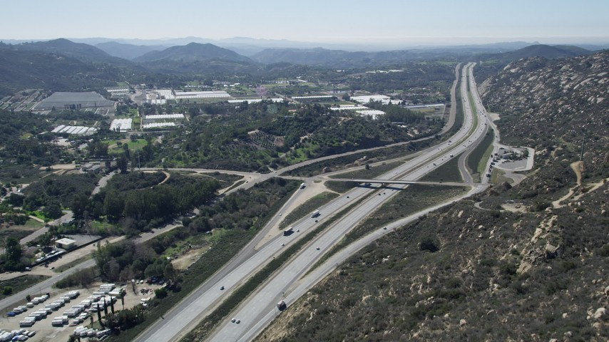 5K aerial video of following light traffic on interstate through farmland, Temecula, California Aerial Stock Footage | AX0015_007