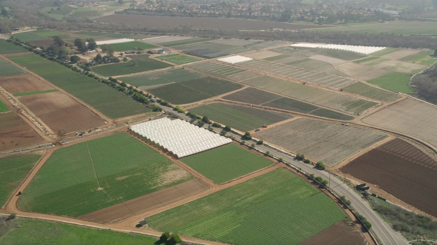 5K aerial  video of farmland and greenhouses beside a country road, Oceanside, California Aerial Stock Footage | AX0015_044