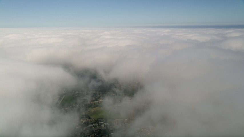 5K stock footage aerial video of flying over a small break in thick cloud cover beneath blue skies, California Aerial Stock Footage | AX0015_051