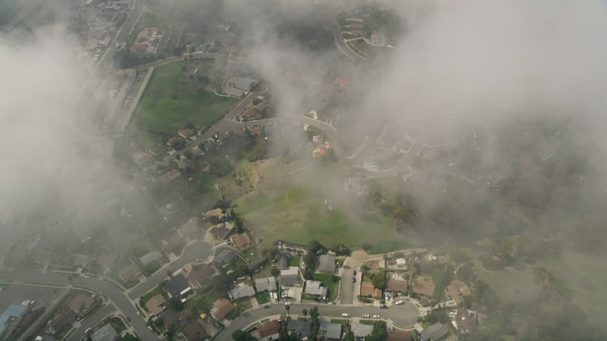 5K stock footage aerial video of a bird's eye of residential neighborhoods through clouds, Oceanside, California Aerial Stock Footage | AX0015_052