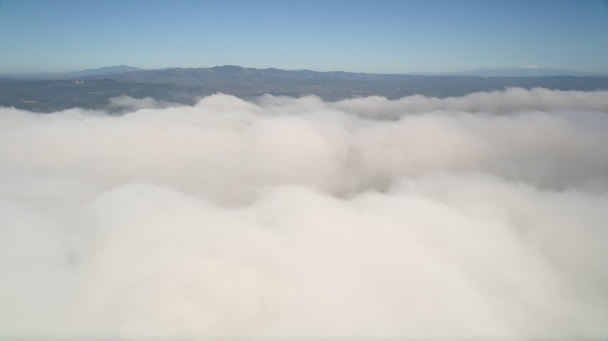 5K stock footage aerial video of passing a thick cover of clouds below blue skies, California Aerial Stock Footage | AX0015_054