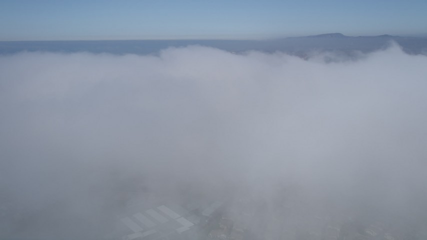 5K stock footage aerial video fly over a dense cover of clouds below blue skies in California Aerial Stock Footage | AX0015_055