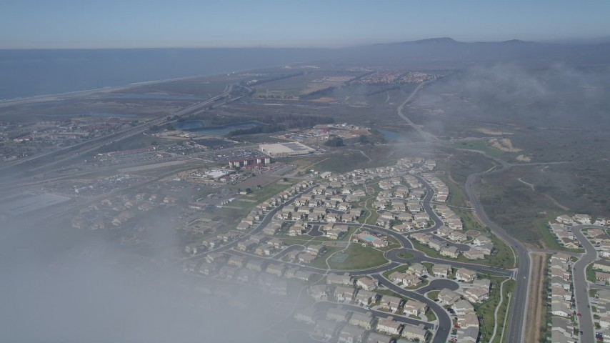 5K stock footage aerial video fly over a dense cloud to reveal tract homes in a suburban neighborhood, Oceanside, California Aerial Stock Footage | AX0015_056