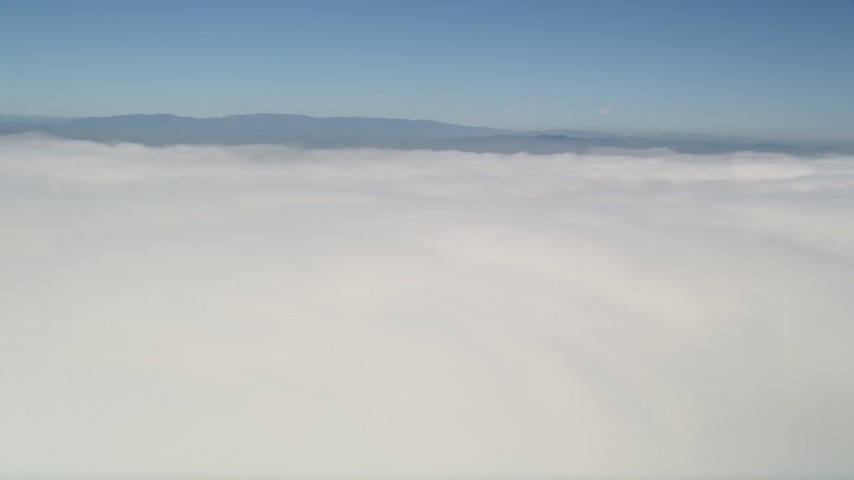 5K stock footage aerial video pan across a thick layer of clouds with blue skies overhead, California Aerial Stock Footage | AX0016_005