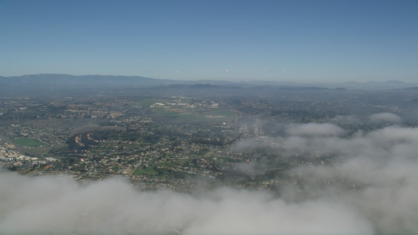 5K stock footage aerial video pan across cloud cover to reveal suburban neighborhoods in Oceanside, California Aerial Stock Footage | AX0016_007