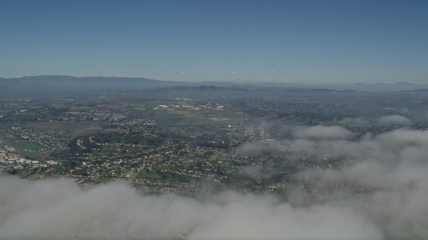 5K aerial video pan across cloud cover to reveal suburban neighborhoods in Oceanside, California Aerial Stock Footage | AX0016_007