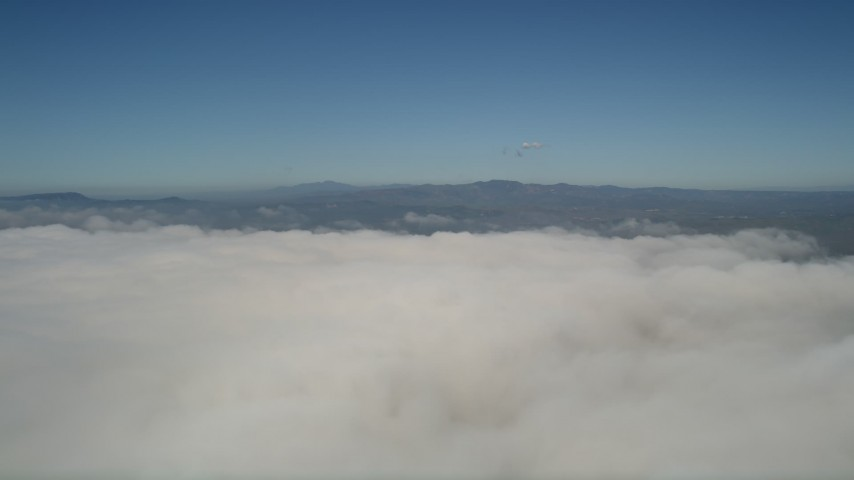 5K stock footage aerial video flyby and pan across a thick layer of clouds to reveal the edge of the layer in California Aerial Stock Footage | AX0016_011
