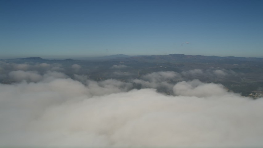 5K aerial video pan across the top of the clouds to reveal the edge of the layer, Oceanside, California Aerial Stock Footage | AX0016_013