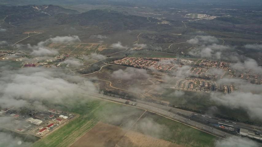 5K aerial video flyby neighborhoods, and pan to military base below cloudy skies, Oceanside, Camp Pendleton, California Aerial Stock Footage | AX0016_022