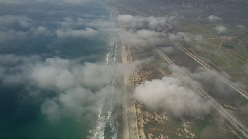 5K stock footage aerial video of an empty beach, follow the coast and fly over clouds, Oceanside, California Aerial Stock Footage | AX0016_027