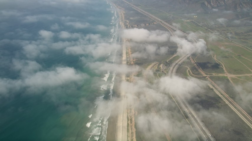 5K aerial video tilt from a bird's eye of the beach and fly over clouds to follow the coast, Oceanside, California Aerial Stock Footage | AX0016_028