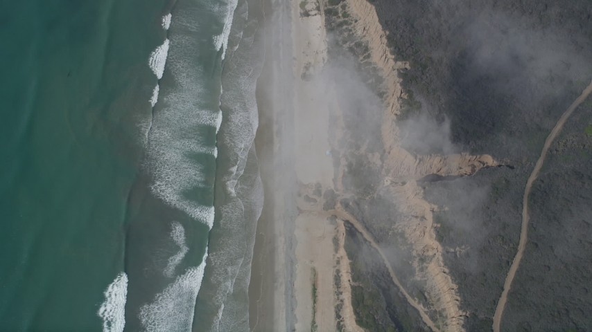 5K stock footage aerial video of a bird's eye of ocean waves rolling toward empty beach and cliffs, Oceanside, California Aerial Stock Footage | AX0016_030