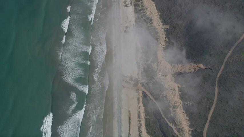 5K aerial video of a bird's eye of ocean waves rolling toward empty beach and cliffs, Oceanside, California Aerial Stock Footage | AX0016_030