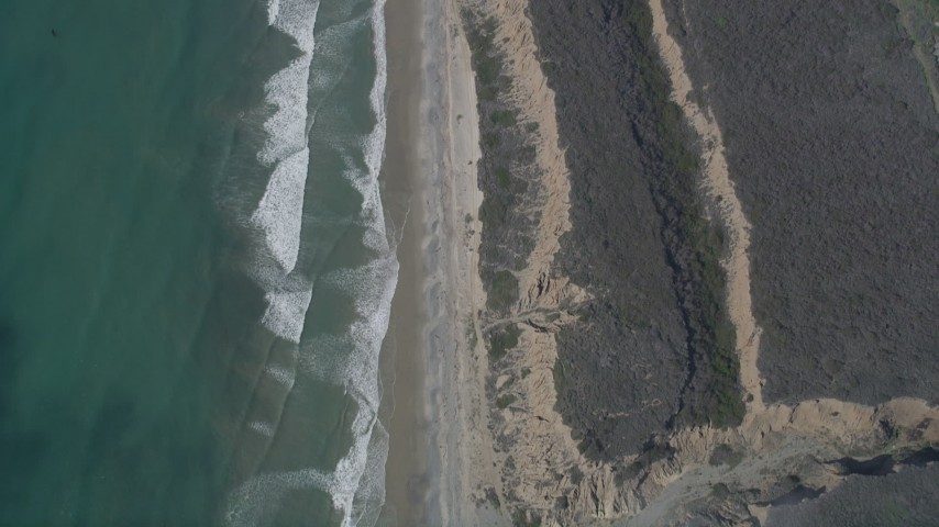 5K aerial video of a bird's eye view of waves rolling toward beach and coastal cliffs, Oceanside, California Aerial Stock Footage | AX0016_031