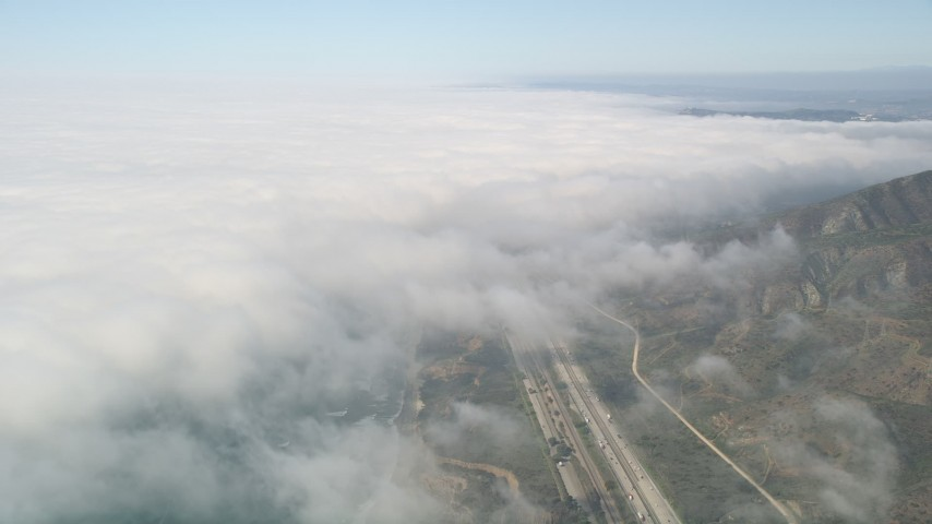 5K stock footage aerial video tilt from empty beach and I-5 to reveal heavy cloud cover, Oceanside, California Aerial Stock Footage | AX0016_032