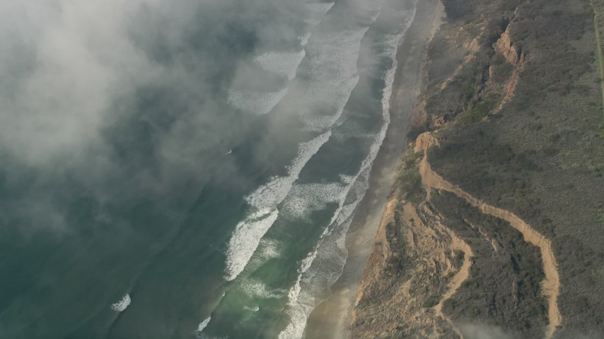 5K stock footage aerial video of a bird's eye of ocean waves rolling toward a beach and cliffs, Oceanside, California Aerial Stock Footage   AX0016_033E