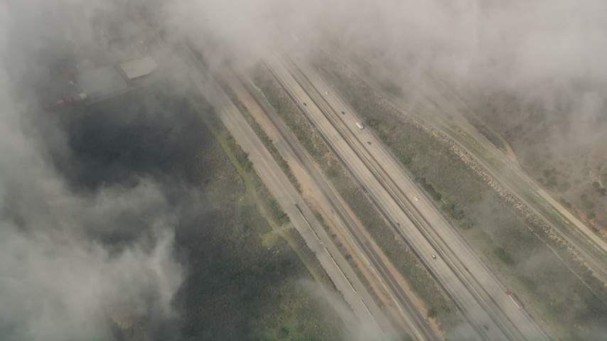 5K aerial video of a bird's eye of light traffic on Interstate 5 through dense clouds, Oceanside, California Aerial Stock Footage | AX0016_035