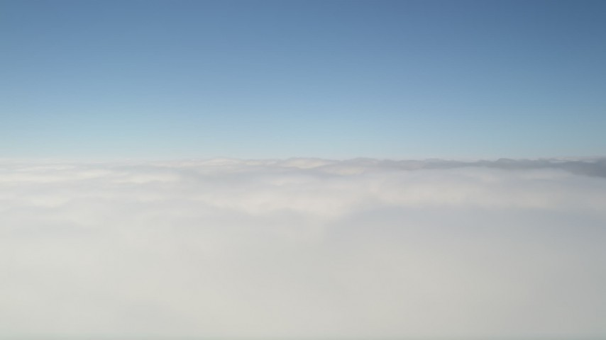 5K stock footage aerial video fly over thick cloud coverage and tilt up to blue sky, California Aerial Stock Footage   AX0016_045