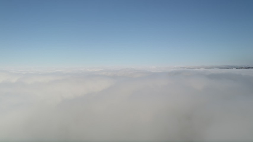 5K stock footage aerial video pan across cloud cover and a break in the clouds, with blue skies above, California Aerial Stock Footage | AX0016_046