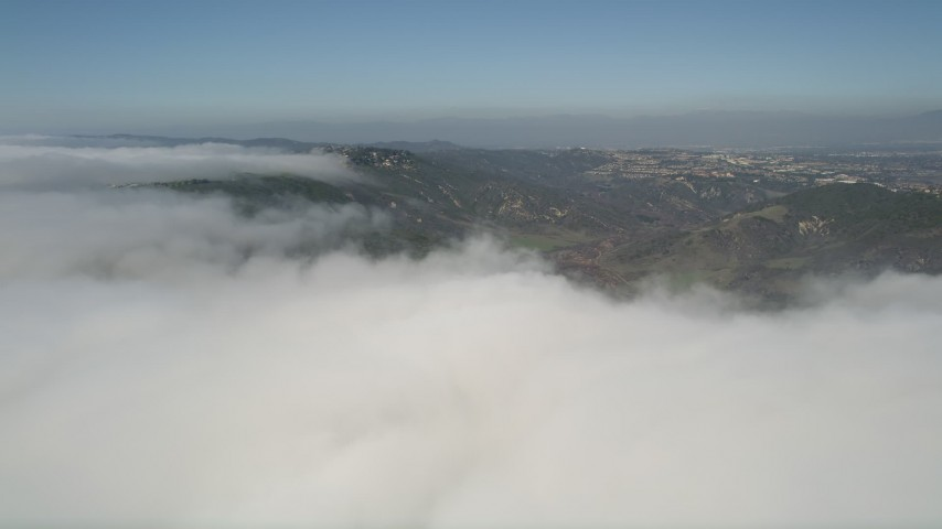 5K aerial video approach the edge of a layer of clouds and hills, Laguna Niguel, California Aerial Stock Footage | AX0016_053