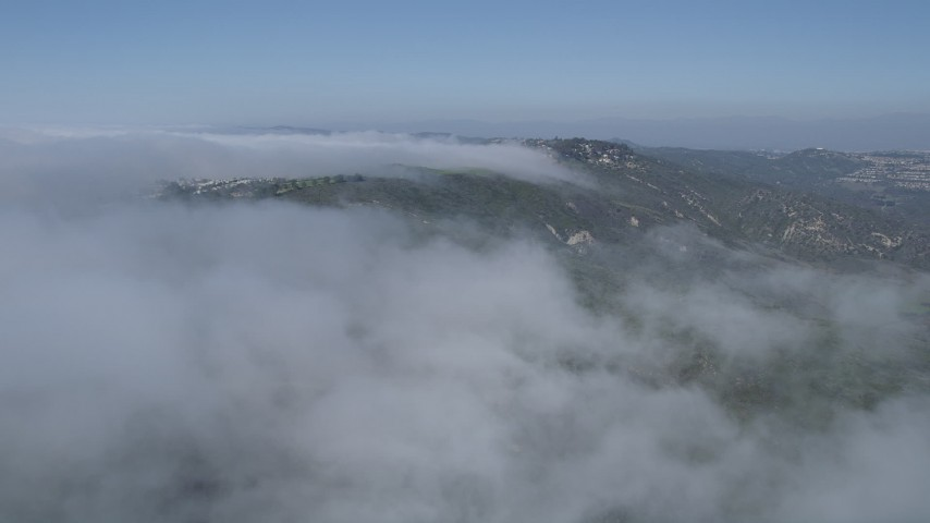 5K aerial video follow the edge of the clouds to approach hillside homes, Laguna Niguel, California Aerial Stock Footage | AX0016_054