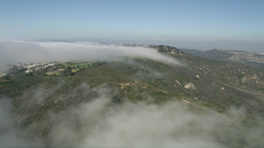 5K stock footage aerial video follow the edge of the clouds to approach hillside homes, Laguna Niguel, California Aerial Stock Footage | AX0016_054E