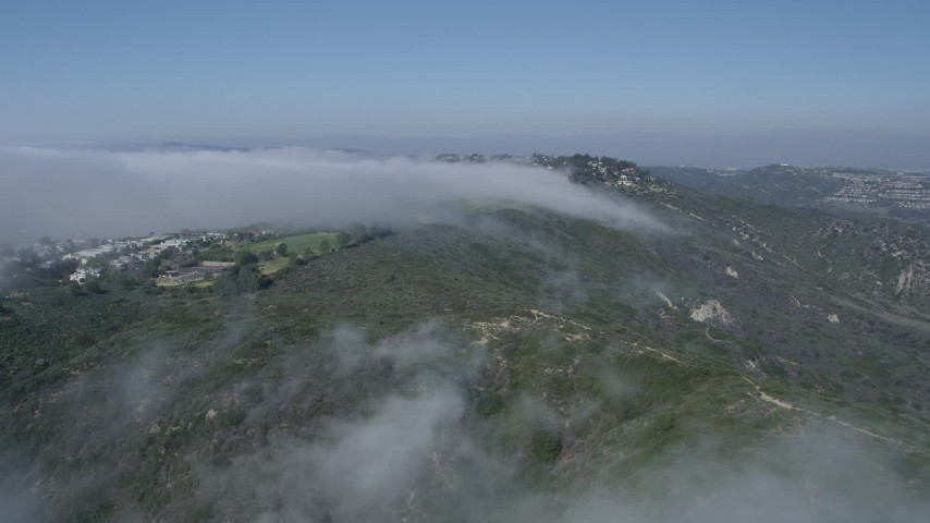 5K aerial video approach a hillside neighborhood with fog rolling over the hills, Laguna Niguel, California  Aerial Stock Footage | AX0016_055