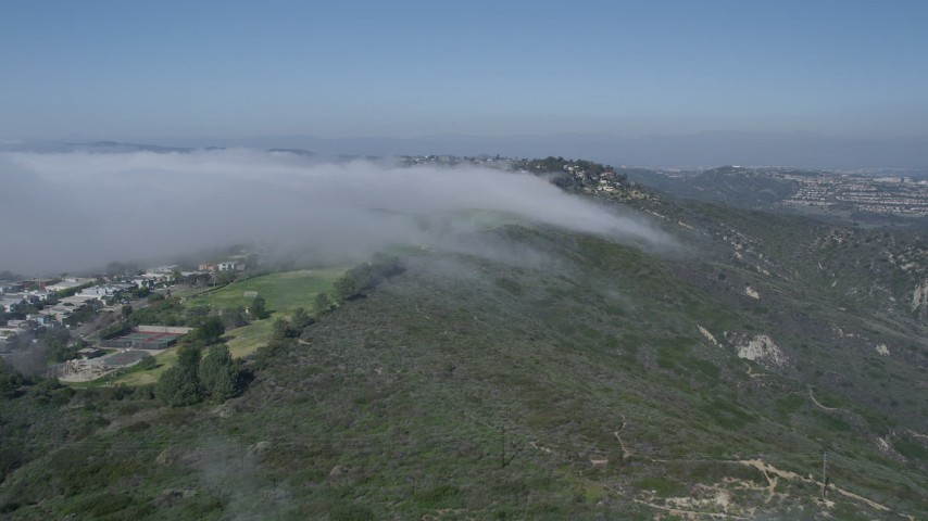5K aerial video approach fog rolling over a hill near hillside homes, Laguna Niguel, California Aerial Stock Footage | AX0016_056