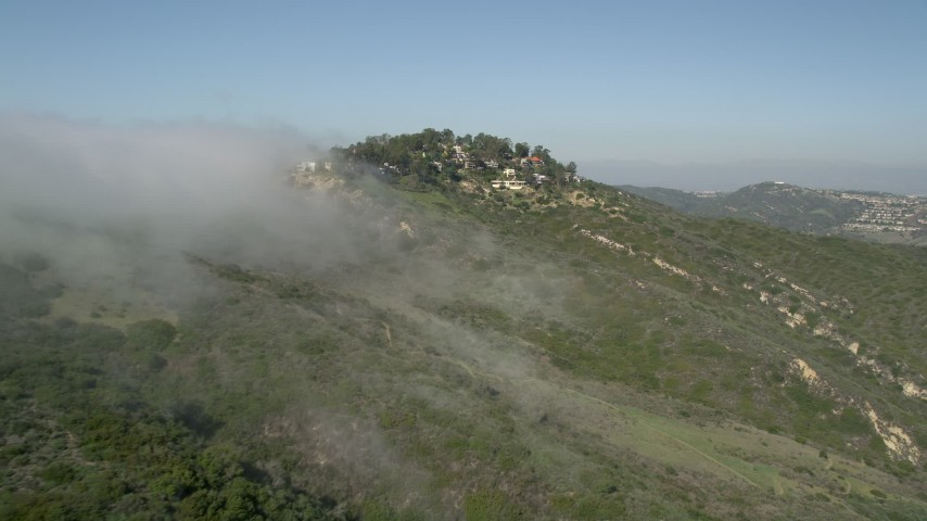 5K stock footage aerial video approach fog rolling over a hill near hillside homes, Laguna Niguel, California Aerial Stock Footage | AX0016_056E