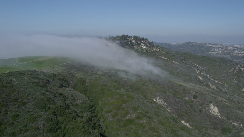 5K aerial video of flying by fog rolling over a hill to approach upscale, hillside neighborhood, Laguna Niguel, California Aerial Stock Footage | AX0016_057