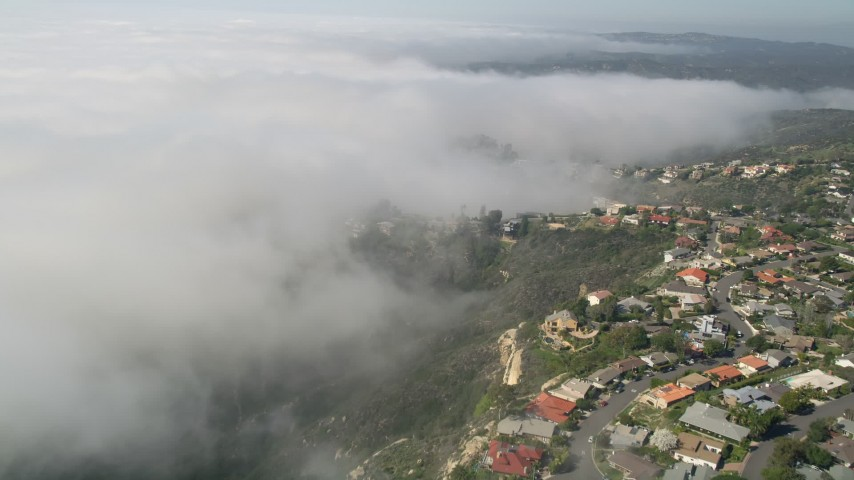 5K aerial video tilt and fly over upscale, hillside homes and a fog bank in Laguna Niguel, California Aerial Stock Footage | AX0016_059