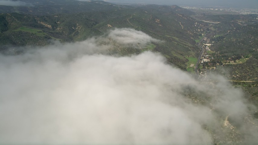 5K stock footage aerial video of green hills by the edge of a fog bank, Laguna Beach, California Aerial Stock Footage | AX0016_061