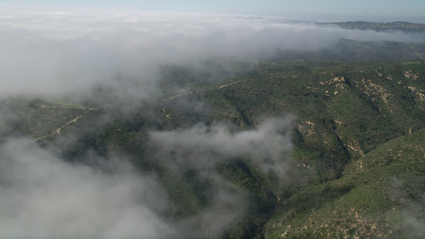 5K aerial video approach a dirt road atop hills near the edge of rolling fog, Laguna Beach, California Aerial Stock Footage | AX0016_062