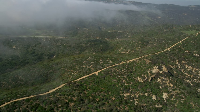 5K aerial video fly over and pan across a dirt road on a hill near rolling fog, Laguna Beach, California Aerial Stock Footage | AX0016_063