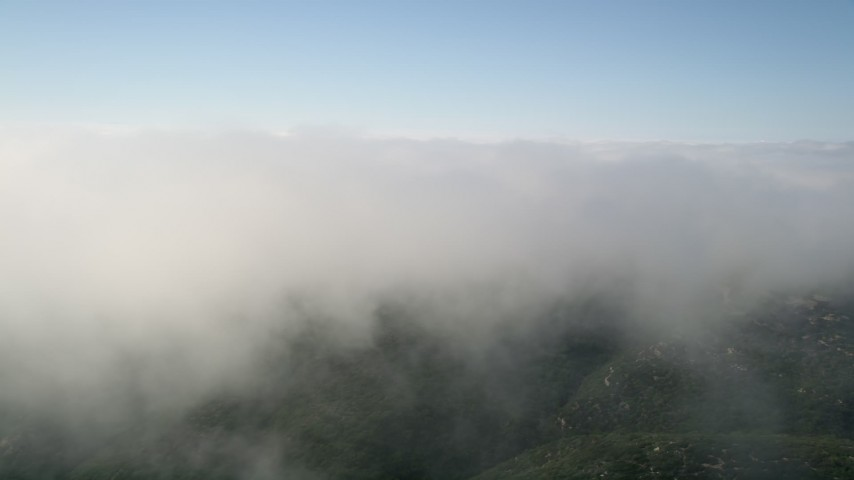 5K stock footage aerial video of flying by the edge of a cloud bank, Laguna Beach, California Aerial Stock Footage | AX0016_065