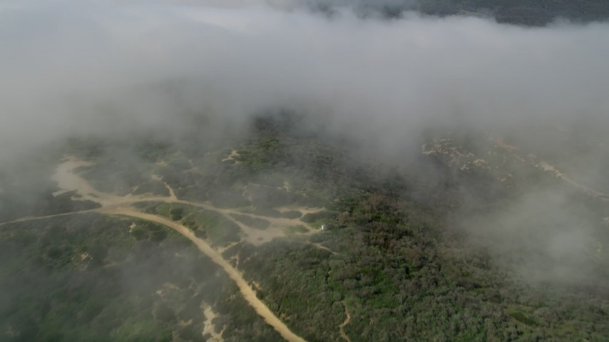 5K stock footage aerial video tilt from fog over the hills to reveal and approach hilltop homes, Laguna Beach, California Aerial Stock Footage | AX0016_066