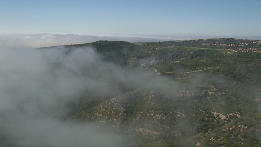 5K stock footage aerial video fly over fog over green hills near hilltop homes in Newport Beach, California Aerial Stock Footage | AX0016_067