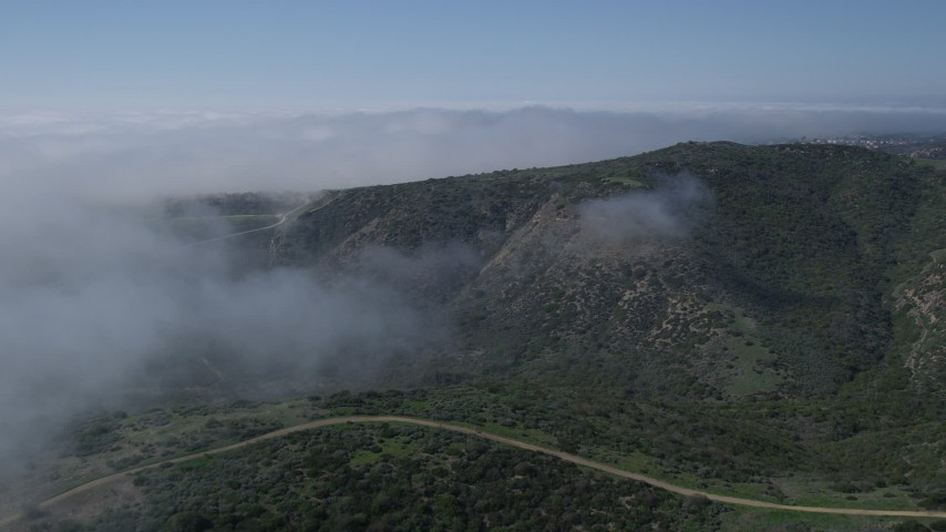 5K aerial video fly over hills and fog toward mountains ridge in Newport Beach, California Aerial Stock Footage | AX0016_068