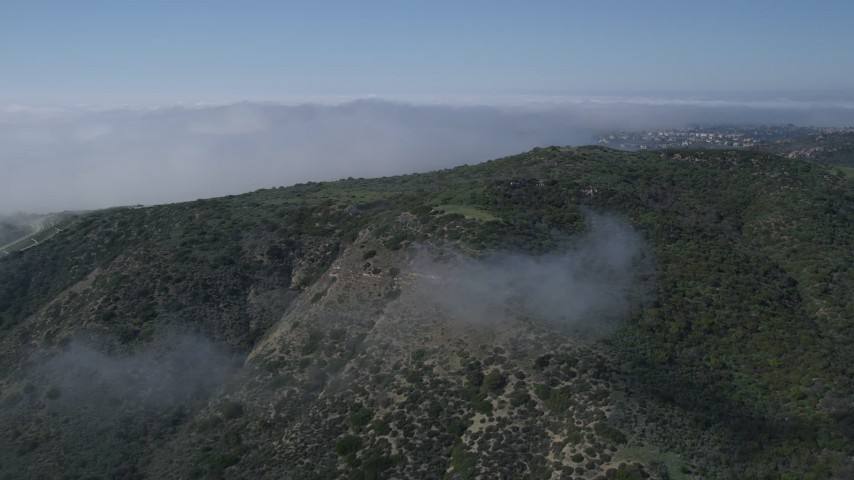 5K stock footage aerial video approach a hill with fog and hilltop homes in the background, Newport Beach, California Aerial Stock Footage | AX0016_069