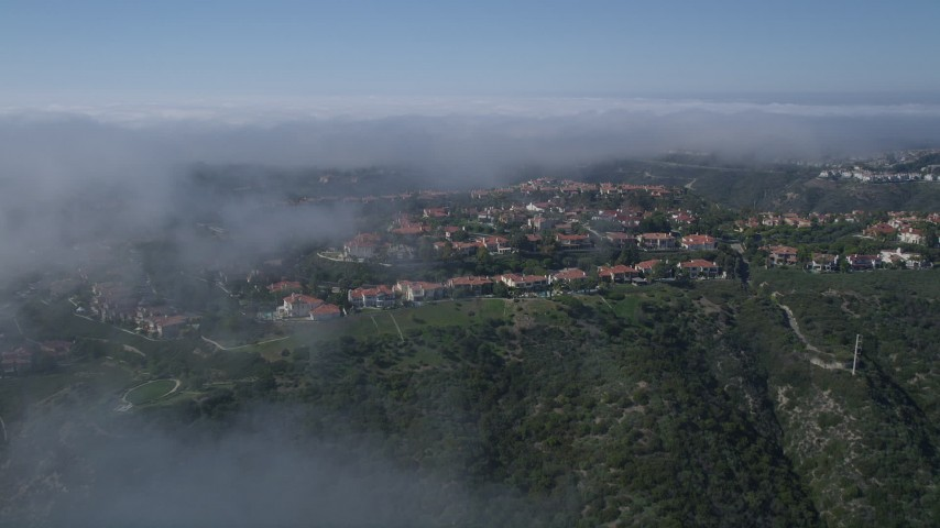 5K aerial video approach and fly over hilltop mansions near a fog bank, Newport Beach, California Aerial Stock Footage | AX0016_070