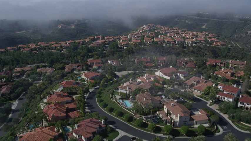 5K stock footage aerial video fly over large, upscale homes to approach a fog bank, Newport Beach, California Aerial Stock Footage | AX0016_071