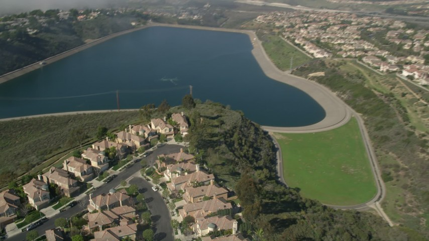 5K stock footage aerial video track a group of homes in a residential neighborhood by the San Joaquin Reservoir, Newport Beach, California Aerial Stock Footage | AX0016_074