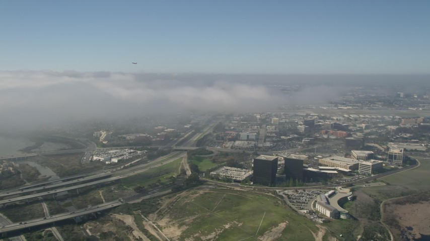 5K stock footage aerial video track an airliner ascending over a fog bank, seen from office buildings beside Highway 73, Newport Beach, California Aerial Stock Footage | AX0016_079
