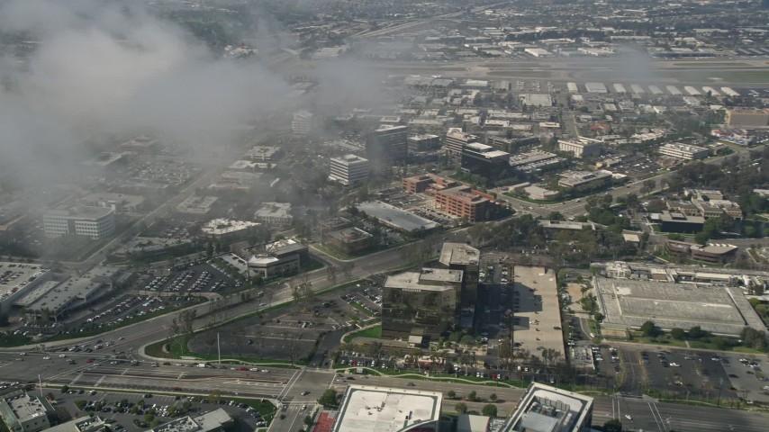 5K aerial video tilt down to office buildings on MacArthur Boulevard, seen through misty clouds, Newport Beach, California Aerial Stock Footage | AX0016_081