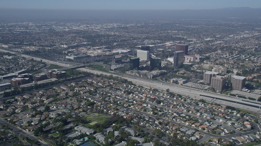 5K aerial video fly over homes to approach office buildings on the other side of Interstate 405, Costa Mesa, California Aerial Stock Footage | AX0016_085